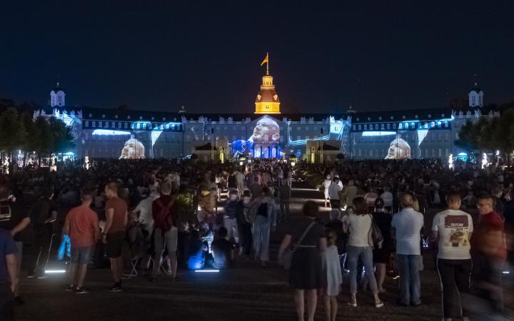 Auf der Schlossfassade erscheint eine kurze Ansprache vom Astronauten Alexander Gerst an seine noch nicht geborenen Enkel. Es ist ein Ausschnitt eines Internet-Video, welches bereits millionenfach geklickt wurde.