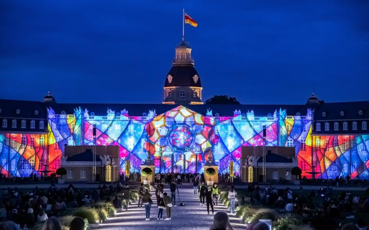 Photo of a colorful projection mapping at night on the baroque Karlsruhe castle.