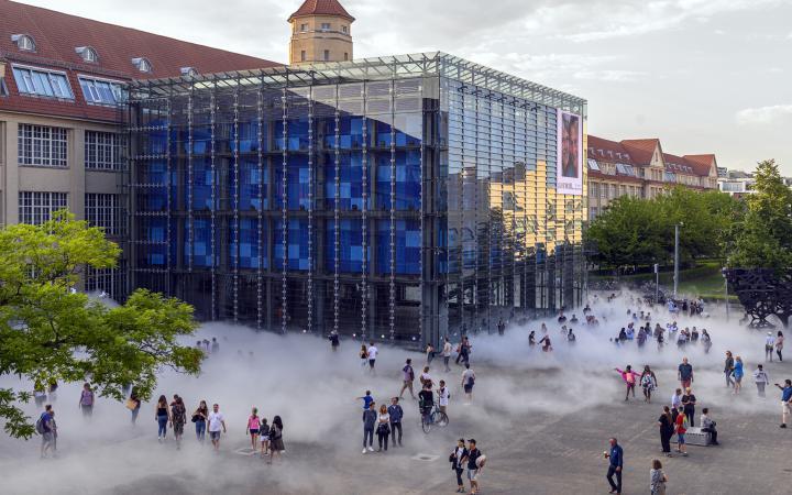 Das Foto wurde mit einer Drohne aufgenommen und zeigt den Kubus des ZKM bei Tag. Drum herum sind eine Menge Menschen versammelt die hinter der Nebelskulptur zum Teil verdeckt werden.