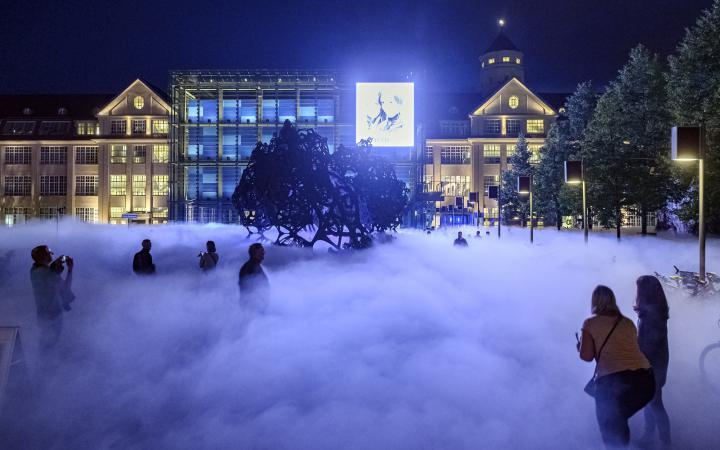 Auf dem Foto sieht man die Nebelskulptur bei Nacht. Das Foto zeigt den die hell erleuchtete Fassade des ZKM Gebäudes und man sieht den Mittelteil mit Kubus und Osteingang