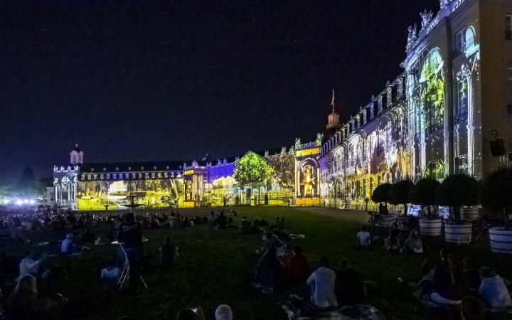 Verschiedene Lebenswelten werden auf die Fassade des dreiflügeligen Karlsruher Schlosses projiziert.