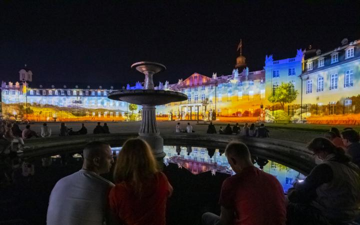 Various living environments are projected onto the façade of the three-winged Karlsruhe Castle.