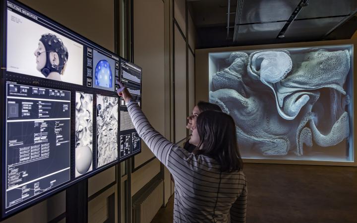 Zwei Frauen stehen vor einem Bildschirm in der Ausstellung »Open Codes. Die Welt als Datenfeld«