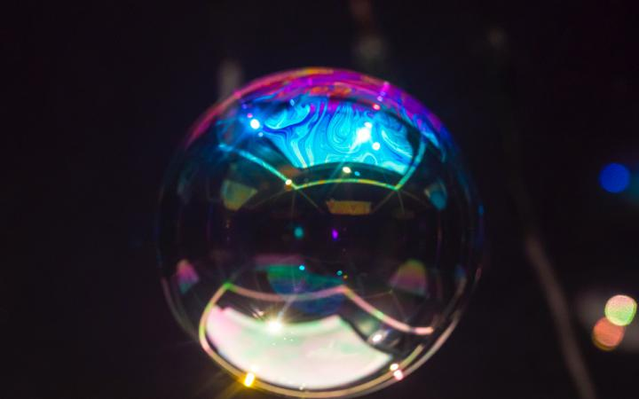 The photo shows a sphere similar to a huge soap bubble in front of a black background.
