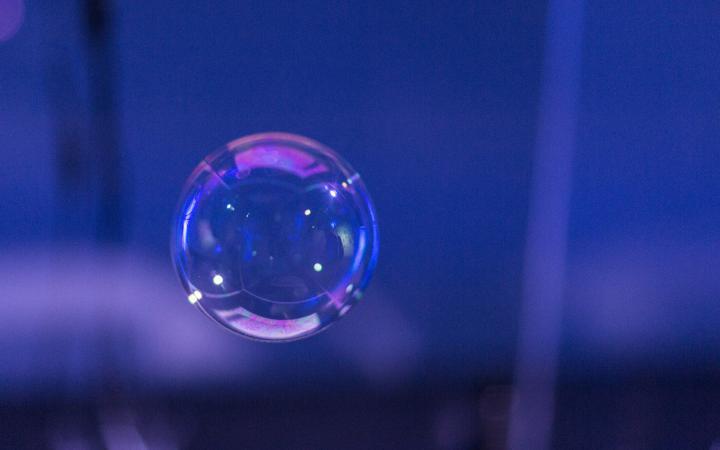 A soap bubble against a violet, dark background.