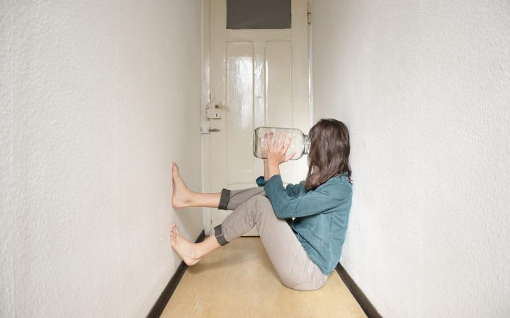 A person is sitting on the flor in a small hallway with the feet at the wall, and is holding an empty jar against her face.