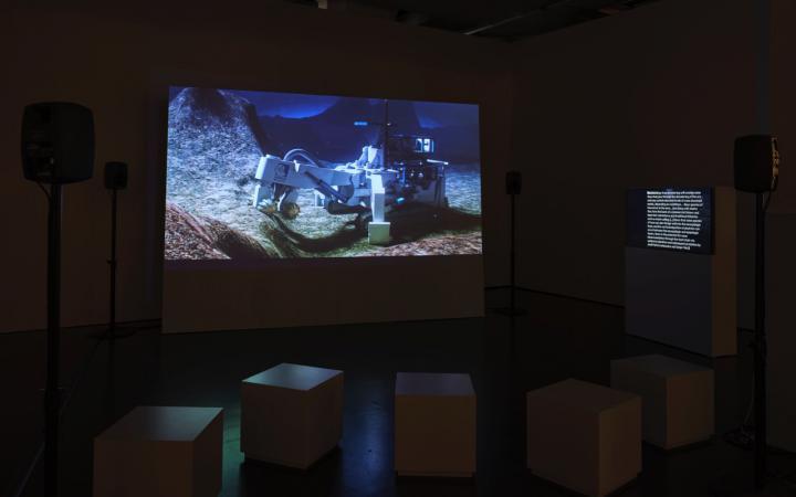 Das Bild zeigt einen Raum mit Sitzkästen, Monitoren und einem großen Bildschirm auf dem der Film »Prospecting Ocean« von Armin Linke abgespielt wird.