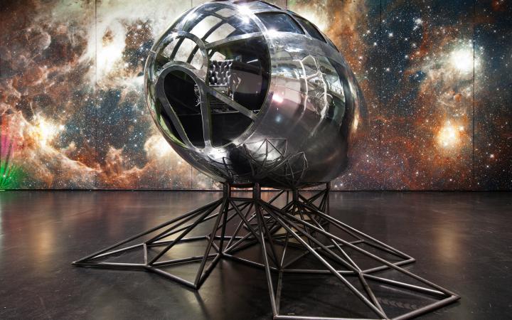 Eine Art Raumschiff steht vor einem Sternenbild