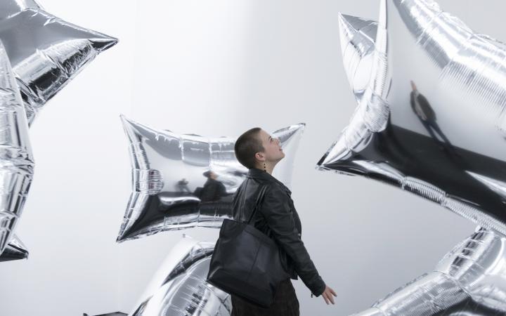 Eine junge Frau mit rechteckigen Silberballons, die durch einen weißen Raum schweben.