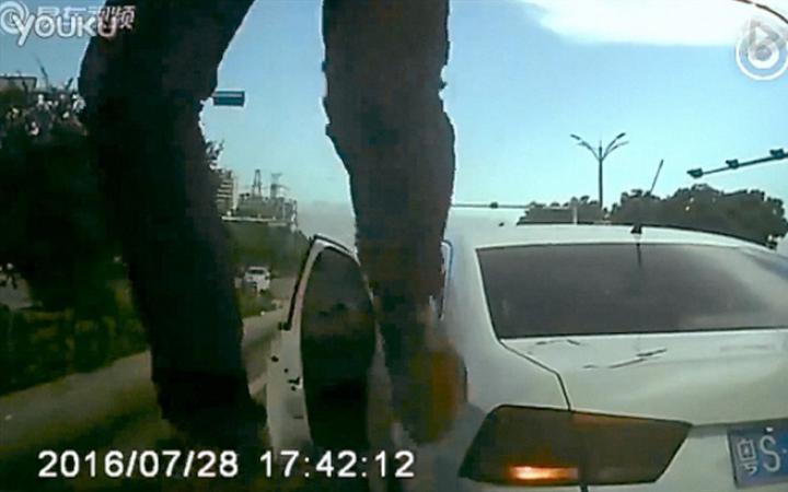 Bild einer Überwachungskamera: Zwei Beine, dahinter ein Taxi