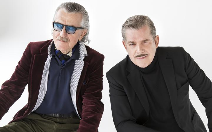 Two men sit next to each other on one ball. They both wear casual suits. The left one wears colored glasses, both wear moustaches.