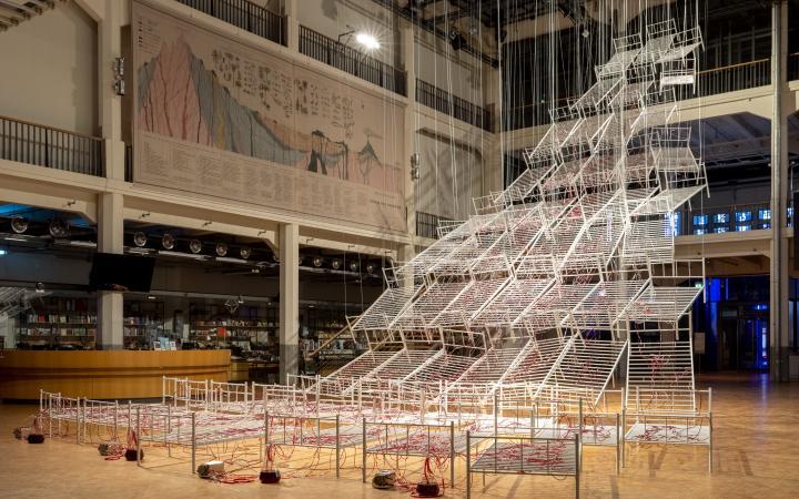 Installationsansicht von Chiaru Shiotas »Connected to Life«. Zu sehen sind Krankenhausbettengestelle, die pyramidenförmig von der Decke hängen. Durchzogen sind diese von Schläuchen, durch die rote Farbe fließt.