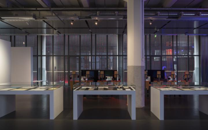Ein weiter Blick in die Ausstellung. Vorne Vitirinentische, links eine Stellwand mit Bildschirmen und Kopfhörern, im Hintergrund mehr Bildschirme und Stühle.