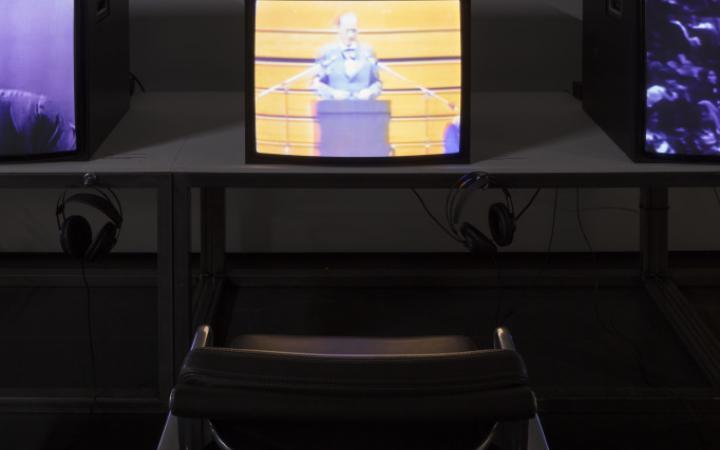 Nahaufnahme einer Videoinstallation. Fernseher auf Tisch mit Kopfhörern und davor ein schwarzes Stuhl.