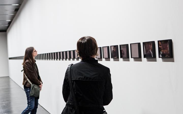 Zu sehen sind zwei Personen, die vor einer langen, waagerechten Anreihung kleider Bilder stehen