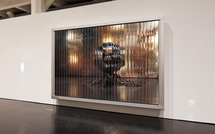 Zu sehen ist ein weißer Rahmen bestückt mit dünnen Spiegelstreifel. Das Spiegelbild zeigt ein silbernes Gestellt, das einer Qualle ähnelt.