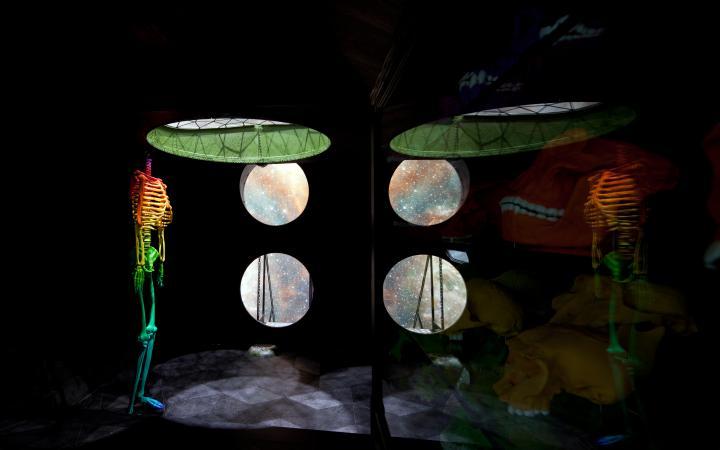 Auf der linken Seite des Bildes ist ein buntes Skelett ohne Kopf zu sehen. Durch ein rundes Fenster in der Decke und zwei kleineren runden Fenstern an der Wand wird dieses von oben und von der Seite beleuchtet. Rechts sieht man die Spiegelung