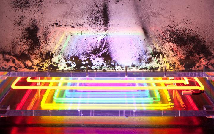 Zu sehen ist eine milchige, rosafarbene Glaswand unter der bund auflleuchtende, quadratisch zusammenlaufende Linien liegen