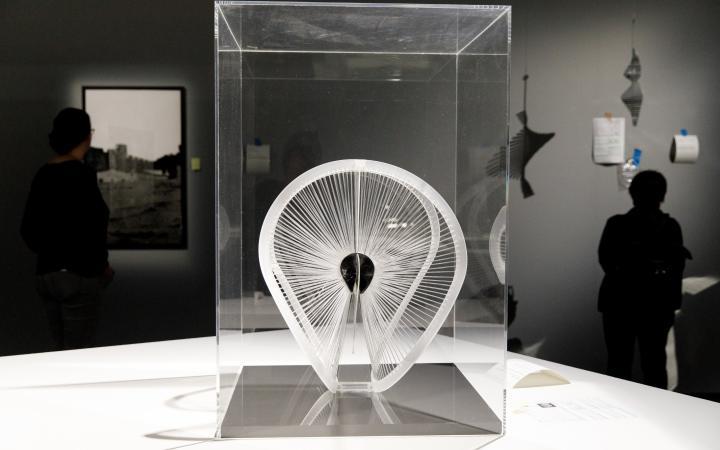 Ein schwungvoll gearbeitetes Kunststoffband ist von zahlreichen Fäden umspannt. Die Fäden sind radial angeordnet wie die Speichen eines Fahrrads.