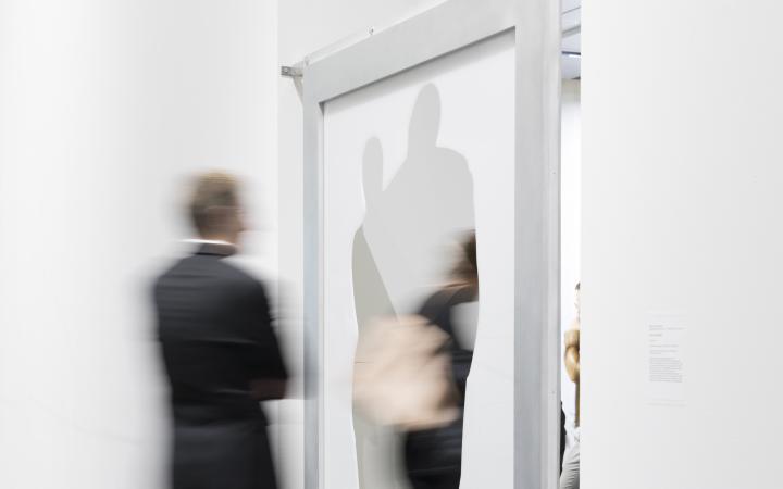 Ein Mensch läuft durch einen scharfwinklingen Stahlrahmen zwischen zwei Räumen.