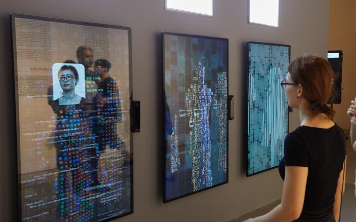 Eine Frau steht vor dem Kunstwerk YOU:R:CODE bestehend aus großen Bildschirmen