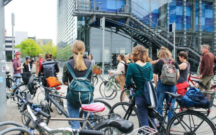 Eine Gruppe von Menschen hat sich mit ihren Fahrrädern vor dem ZKM Kubus versammelt