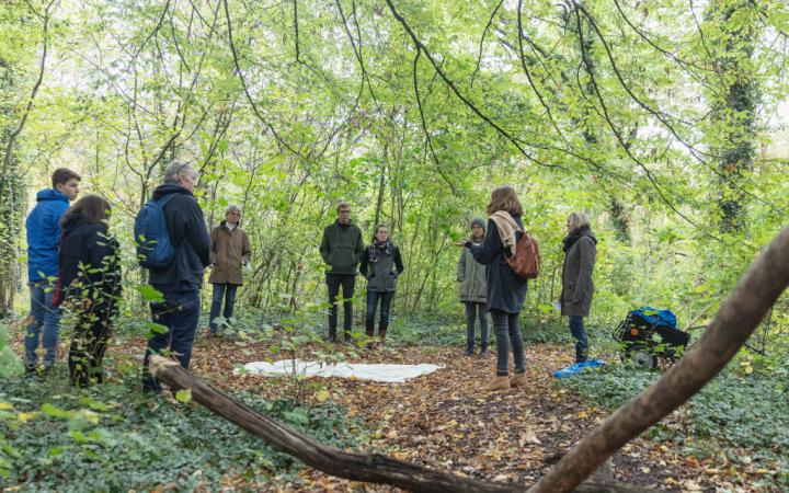 Eine Gruppe Menschen steht im Wald im Kreis um eine sprechende Frau herum.