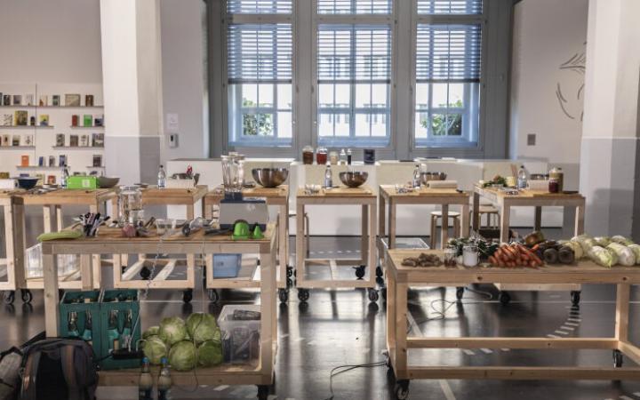 In der ZKM-Ausstellung »Critical Zones« stehen Holztische mit Lebensmitteln und Küchenutensilien.