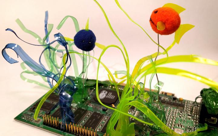 Auf einer Platine sind Blumen aus bunten PET Flaschen aufgelötet.