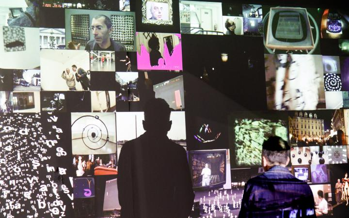 You can see a video installation. Many smaller images are projected onto a wall, creating a mosaic-like image. In front of it stands a man. He casts a conspicuous shadow on the wall.