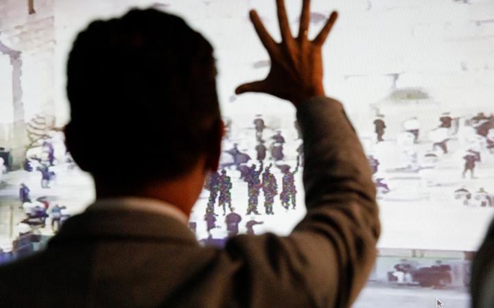Zu sehen ist eine Abbildung an einer Wand, auf der schemenhafte Figuren die Hand zum Gruße heben. Davor steht ein Mann, den Rücken zum Betrachter und hebt ebenfalls seine Hand.
