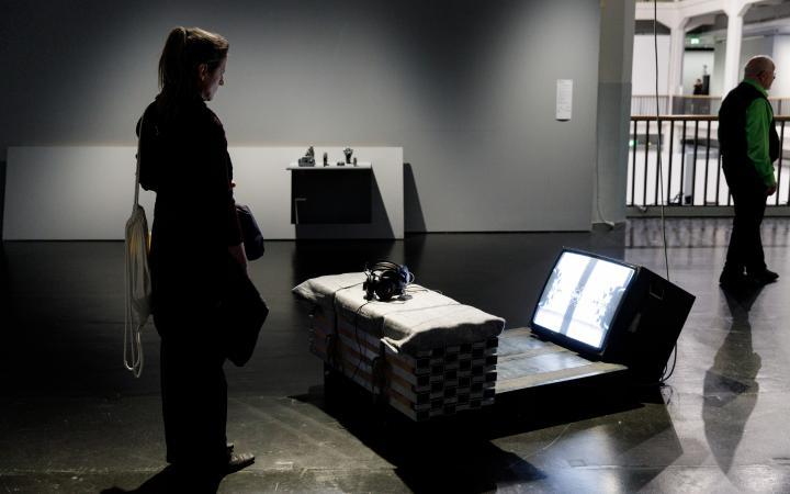 Eine Frau steht vor einer Installation und betrachtet sie. Die Installation besteht aus einer improvisiert aussehender Sitzbank, auf der Kopfhörer liegen. Davor steht auf dem Boden ein Fernseher, dessen Bildschirm 45° nach oben gerichtet ist.