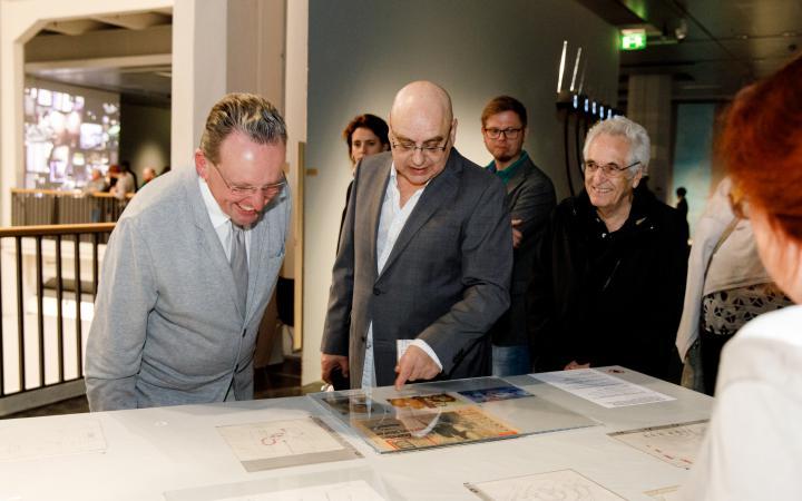 Michael Bielicky zeigt erklärend auf einen Zeitungsartikel, der auf einem Tisch steht. Um ihn herum stehen mehrere Personen, die auf ihn oder auf den Artikel schauen.