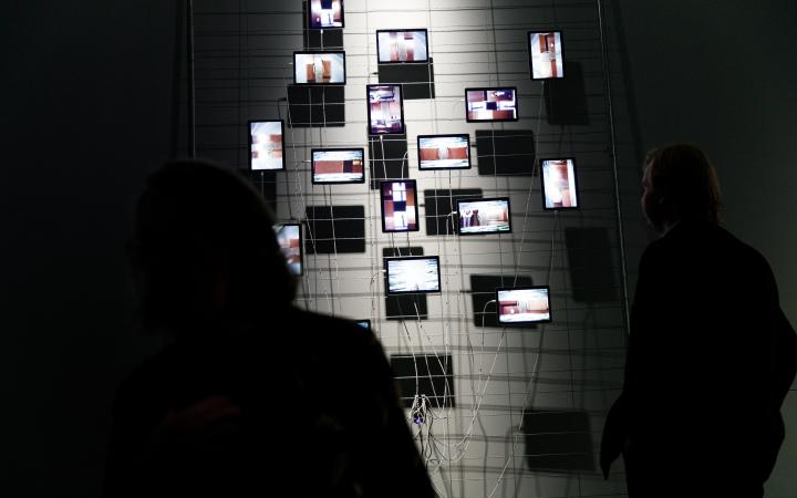 On a metal fence in front of a grey wall hang some tablets which are used as displays. The arrangement is striking, reminiscent of the classic Petersburg hanging. The wiring of the tablets is also notable. A person stands in front of the installation.