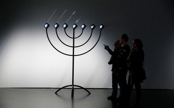 You can see a large, black Menorah with seven small screens with right-facing antennas instead of candles. On the right there are three people looking at it. One of them points to the installation.