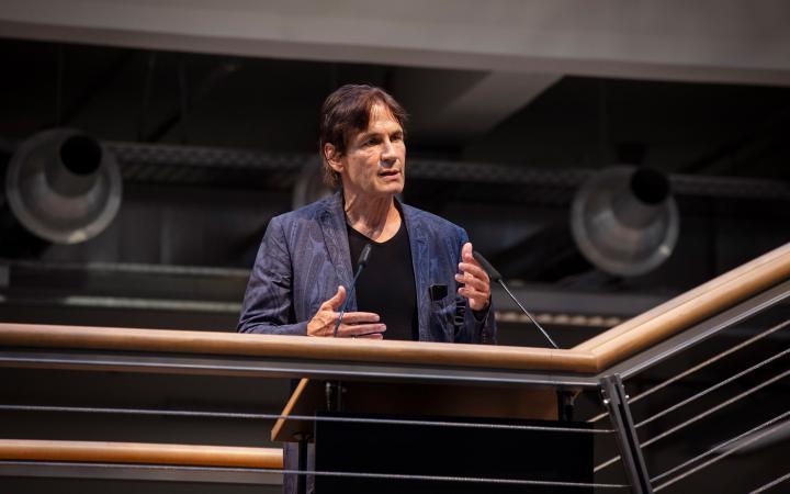Der Künstler Jean-Remy steht auf der ZKM-Foyer-Treppe am Geländer hinter einem Rednerpult und spricht. Seine Gestik begleitet sein Sprechen.