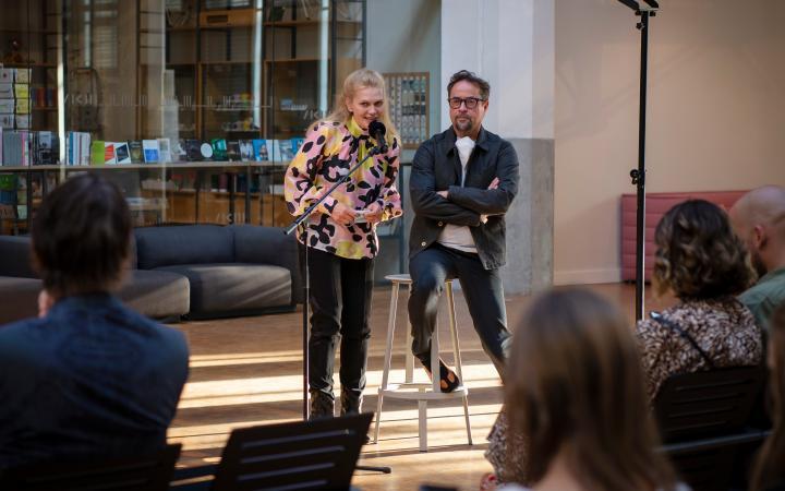 Die SchauspielerInnen Anna Loos und Jan Josef Liefers sind hinter einem Mikrofon. Anna Loos spricht, Jan Josef Liefers sitzt auf einem Hocker, die Arme verschränkt und hört zu.