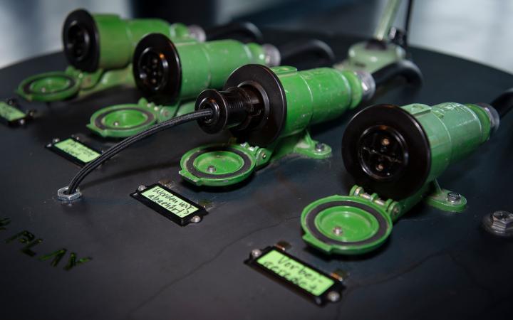 Vier Röhrensteckdosen liegen nebeneinander auf einem Metallpult. Eines davon ist verkabelt. Vor ihnen sind Etiketten befestigt, auf denen etwas geschrieben steht.