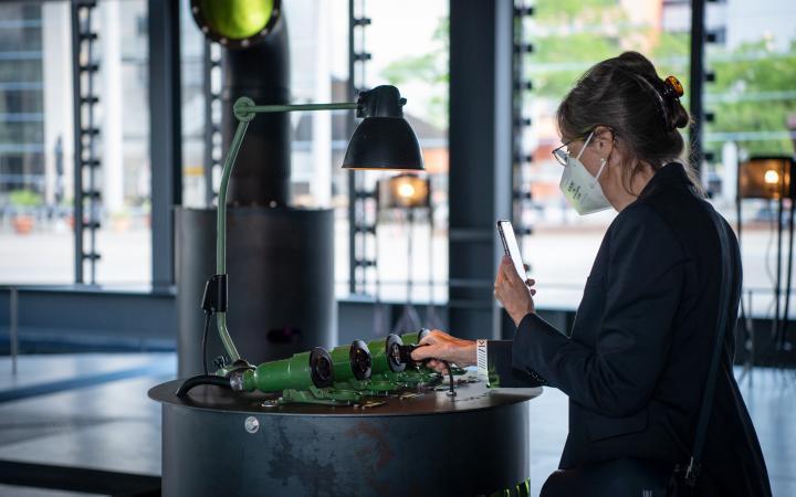 Eine Frau steht vor einer Installation. Mit einer Hand steckt sie den zur Installation gehörenden Stecker in eine der Röhren-Steckdosen. Mit der anderen Hand fotografiert sie ebene jene mit ihrem Handy.