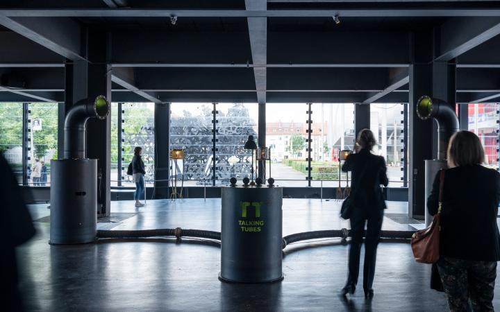 """Ein Raum dessen Wände aus Glas bestehen. In der Mitte befindet sich eine Installatuon aus einem Metallzylinder mit der Aufschrift """"Talking Tubes"""". Zwei Schläuche verbinden links und rechts die Zylinderform mit jeweils einer großen Röhre."""