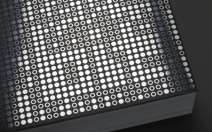 """Vorderseite des Buchs """"A little Known Story about a Movement, a Magazine, and the Computer's Arrival in Art"""": leere und ausgefüllte silberne Kreise auf schwarzem Grund, die Binärcode symbolisieren"""