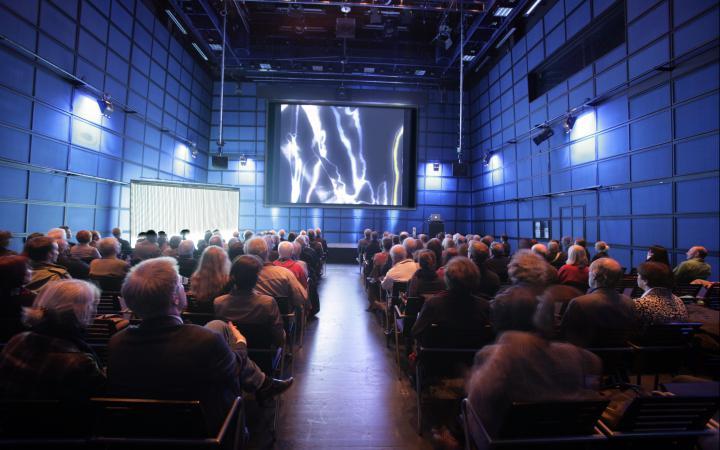 Das ZKM_Medientheater voller Menschen, die auf eine Leinwand schauen, auf der amorphe Strukturen in weiß zu sehen sind