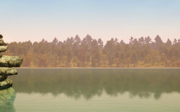 """The image shows a clip from the video game """"Walden a Game"""". You can see a wide lake with trees at its edge. On the left are stones piled up to form a meditative sculpture"""