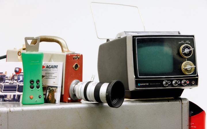 Ein sehr alter, kleiner TV-Monitor, eine alte Videokamera und eine Fernbedienung mit integriertem Flaschenöffner