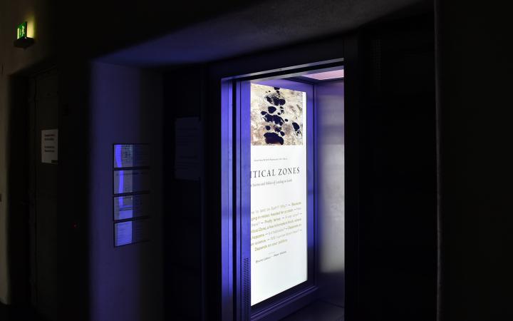 Zu sehen ist ein geöffneter Fahrstuhl. An der Innenwand des Fahrstuhls befindet sich ein großer Display, welcher einen Text zu der Ausstellung Critical Zone zeigt.