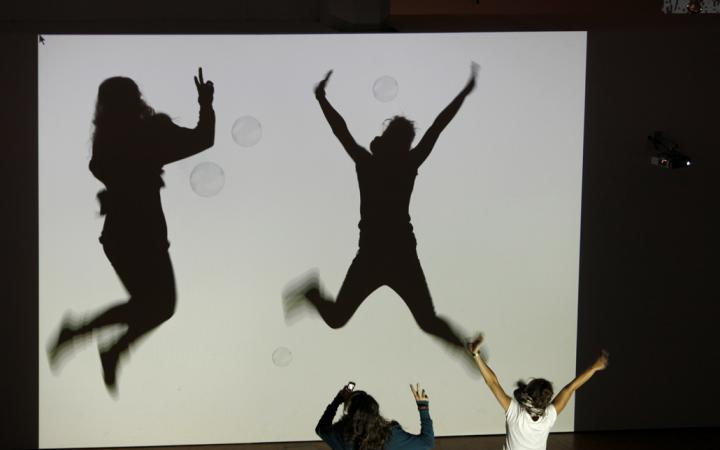 Shadows of children who interact with animated bubbles