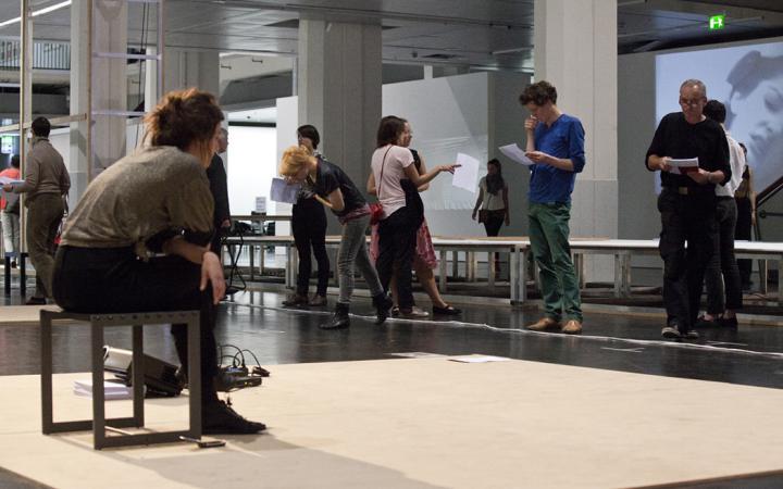 mehrere Personen im Ausstellungsraum, die Texte üben
