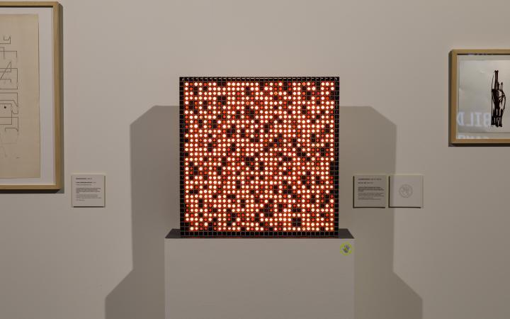 Eine quadratische Box, die aus kleinen Lampen bestehen, die entweder rot leuchten oder aus und schwarz sind