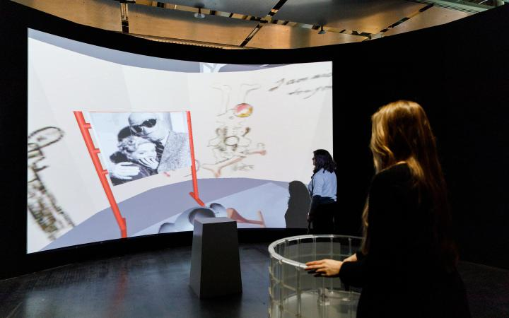 Besucherin vor einer Panorama Leinwand mit VR Anwendung