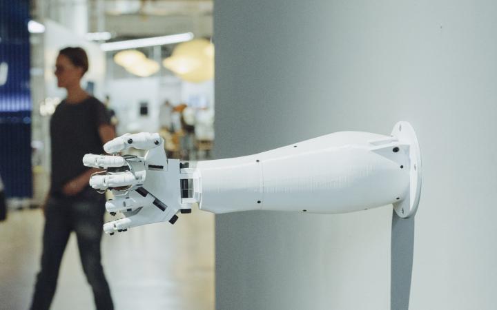 Aus einer Wand ragt eine Roboterarm, dessen Hand etwas umschlossen hält.